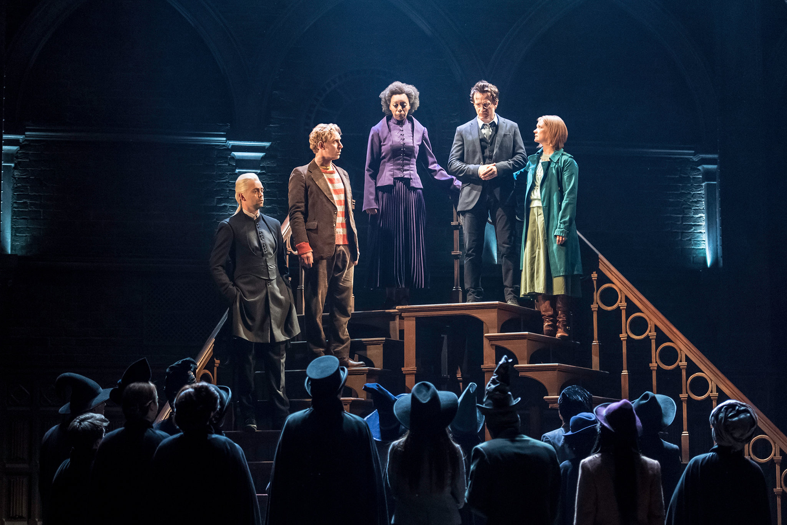 Draco, Rony, Hermione, Harry e Gina no topo de uma escada falando para um monte de bruxos