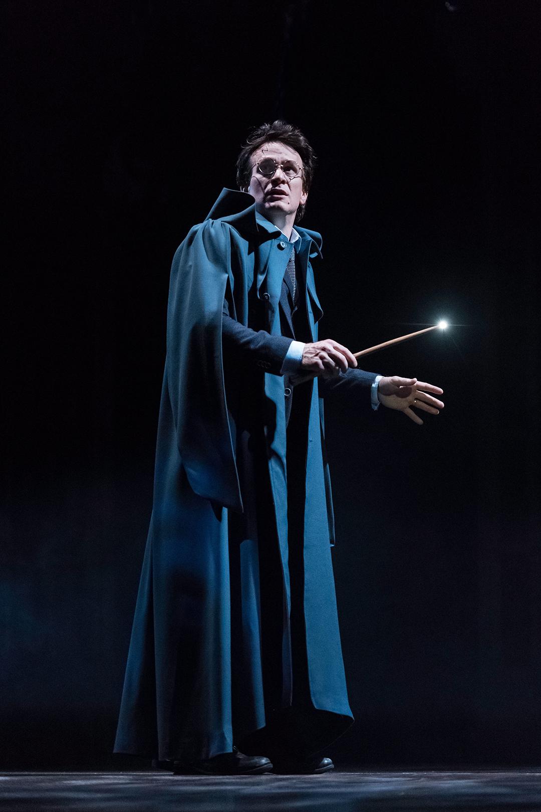 Harry com sua varinha acesa olhando para o alto, assustado.