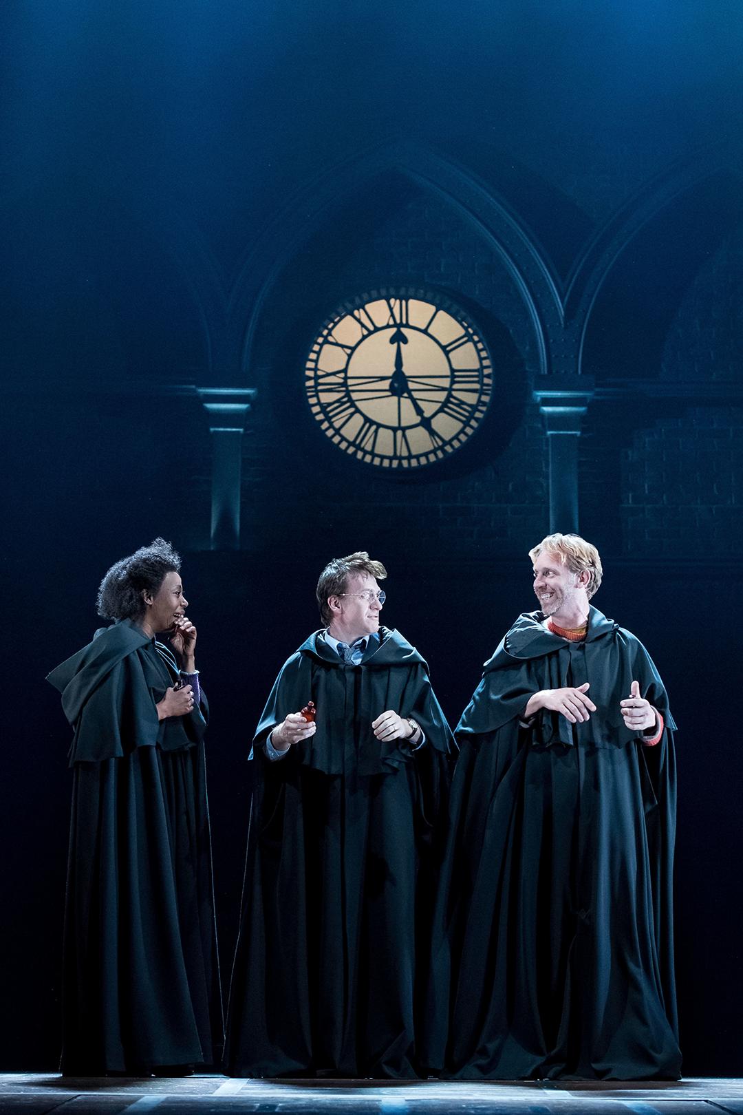 Hermione, Harry e Rony sorrindo uns para os outros em capas negras.