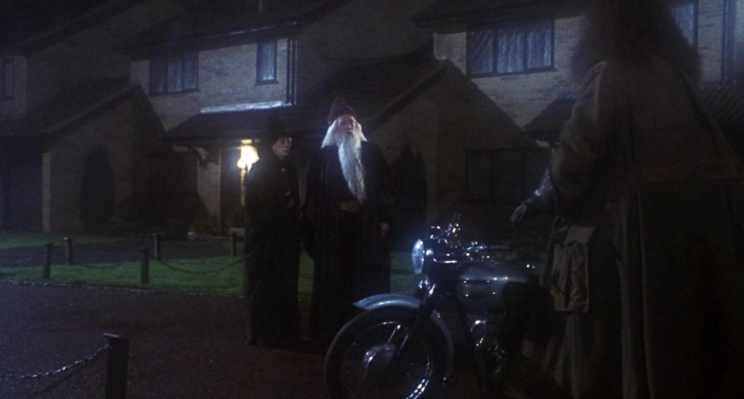 Hagrid traz o bebê Harry ao encontro de Dumbledore e Minerva na frente casa.
