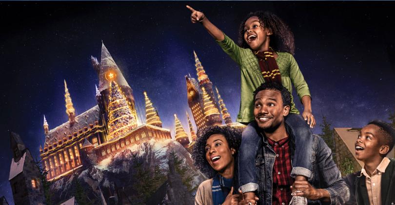 Imagem de divulgação do evento. Nela, uma família de quatro pessoas observam animados o castelo de Hogwarts, que está repleto de neve, luzes de Natal e árvores de Natal. Há um menino e uma menina, e o pai e a mãe deles. A menina está na garupa do pai e aponta para cima. Ela está de cachecol da Grifinória. A esposa está em um dos lados do pai, com um cachecol da Corvinal. Do outro lado dele, está o menino, usando uma capa da Sonserina.