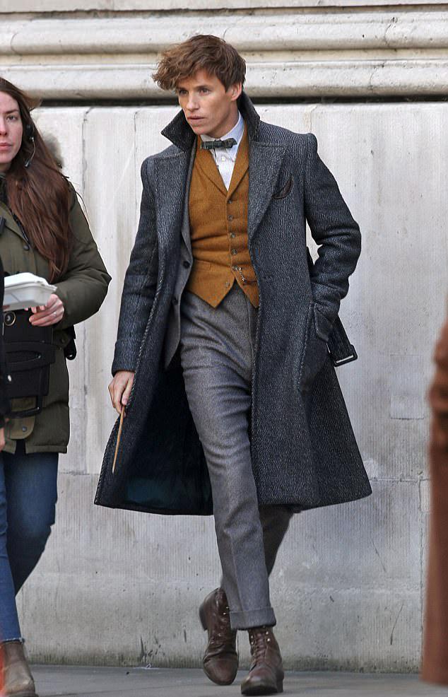 Eddie Redmayne conversa com uma produtora do filme enquanto os dois caminham por uma calçada de Londres.