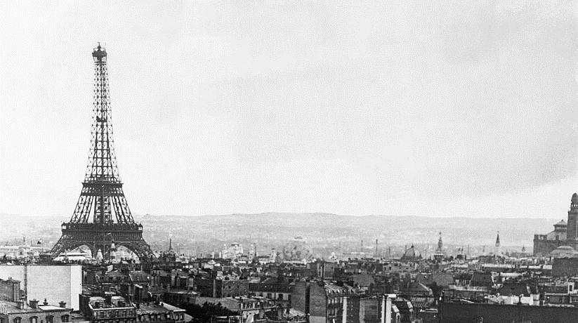 Uma foto de Paris em 1927. A esquerda da imagem dá pra ver a Torre Eiffel, com prédinhos e casas na sua base. A foto não tem cores.