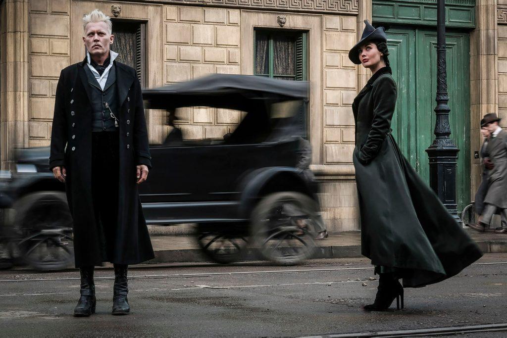 Grindelwald (Johnny Depp) e Rosier (Poppy Corby-Tuech) em pé numa rua. Por trás dele, passa um carro antigo e há um prédio de tijolos beges. Grindelwald veste roupas escuras, exceto por uma camiseta por dentro de um colete, que é branca. Ao seu lado está Rosier, de salto alto, sobretudo feminino preto. Ela usa um chapéu estiloso também preto. Eles parecem estar olhando para algo no céu.