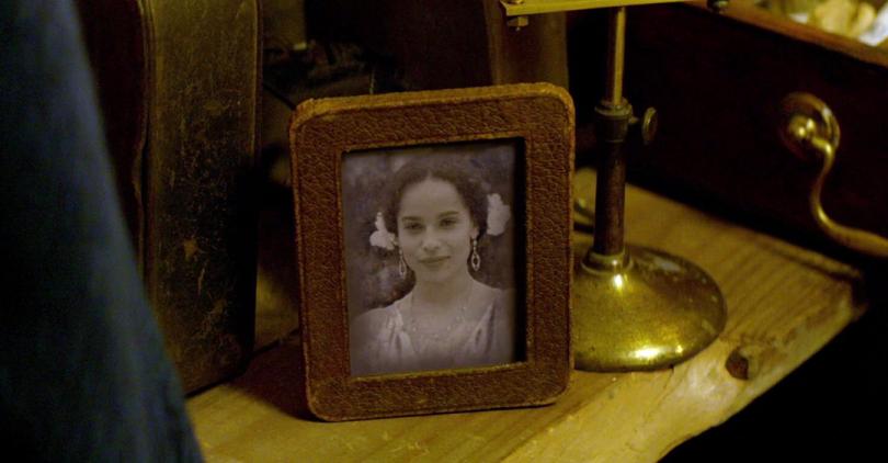 Captura do filme Animais Fantásticos e Onde Habitam. Nela, vemos a personagem Leta Lestrange num porta retrato em meio a outros itens de Newt Scamander. Na foto, Leta está jovem, usa adereços brancos no cabelo, está de vestido branco e sorri.