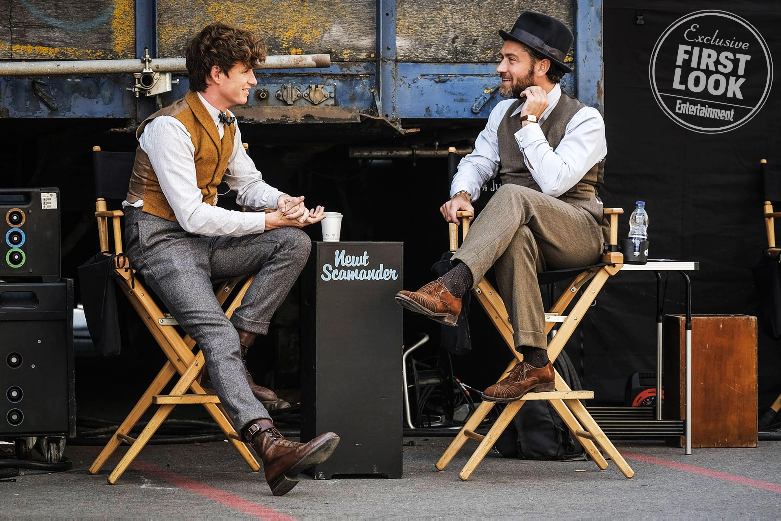 """Eddie Redmayne conversa com Jude Law. Os dois estão sentados em cadeiras dobráveis típicas de estúdio de cinema. Do lado esquerdo de Eddie Redmayne, vemos um equipamento de som. Por trás dos dois atores, há um fundo preto e algo que se assemelha a uma porta de caminhão, com uma tranca. Entre os dois homens, há uma bancada com o nome """"Newt Scamander"""" escrito em uma fonte jovial. Nela, está disposto um copo térmico. Do lado direito de Jude Law, vemos uma garrafa de água em uma bancada diferente. Eddie Redmayne está vestido com as roupas tradicionais de Newt (mas sem o sobretudo). Jude Law está com uma roupa similar (calça social e colete por cima de uma camisa branca, mas com cores mais sóbrias. Além disso, ele está com um chapéu fedora de cor preta."""