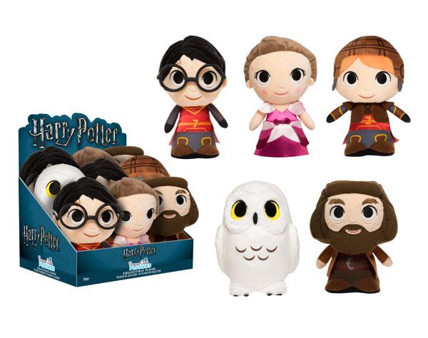 """Na imagem, vemos uma caixa de papelão do tipo mostruário com o logo da série """"Harry Potter"""" em cima e, nela, 9 bonecos amontoados. Ao lado, observamos 5 pelúcias: o primeiro é Harry Potter utilizando o uniforme de quadribol da Grifinória, com o número 7 estampado. A segunda é Hermione Granger em um vestido de gala rosa. A terceira é Rony Weasley usando o uniforme de quadribol da Grifinória de número 2 estampado. Diferentemente de Harry, ele usa ombreiras e um capacete. A quarta pelúcia é a coruja das neves Edwiges, com olhos amarelos. A quinta e última é Rúbeo Hagrid em seu figurino de sempre: sobretudo marrom e roupas marrons."""