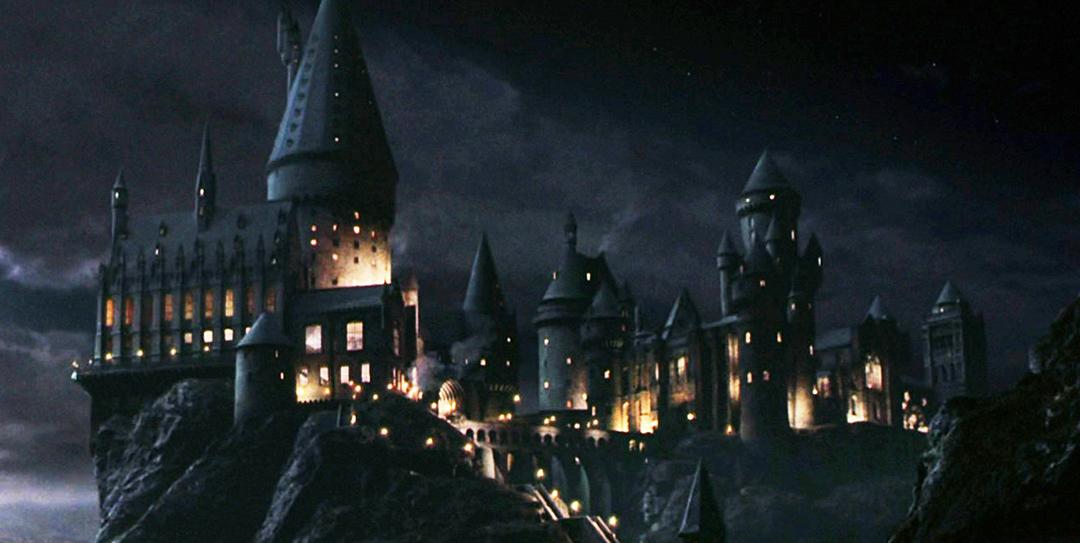 Uma captura de tela de Pedra Filosofal com um plano geral de Hogwarts à noite.