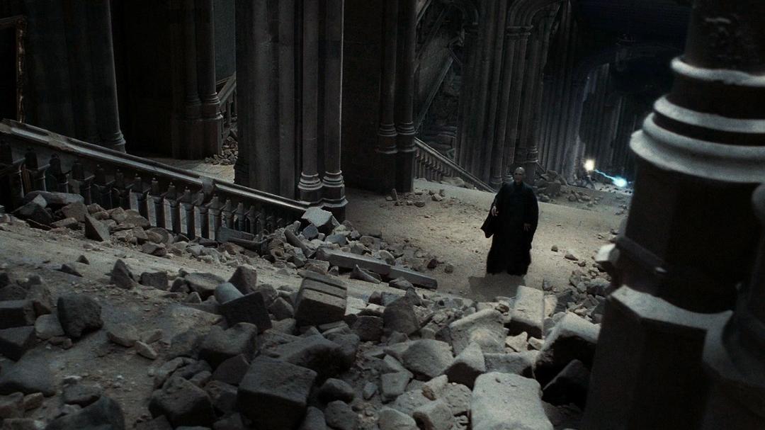 Em uma captura de tela de Relíquias da Morte - Parte 2, Voldemort sobe uma grande escada cheia de entulhos. Ao fundo, há duas pessoas duelando.