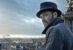 Jude Law, usando um chapéu preto típico dos anos 20 e um casaco azul acinzentado olha pra trás, dramaticamente. Ao fundo, um panorama da cidade de Londres.