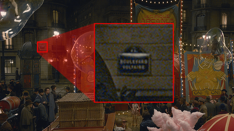 """Na cena que mostra a entrada cheia de gente do circo, há uma placa, ao fundo, que está aumentada na imagem com um zoom. Lê-se """"boulevard Voltaire""""."""