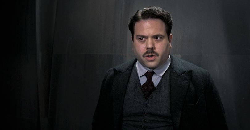 Foto de Dan Fogler como Jacob, com uma expressão de medo em frente a uma parede cinza.