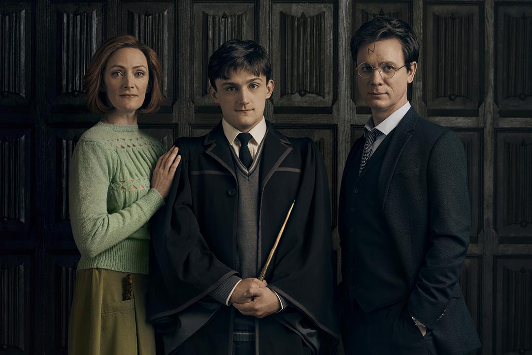 Retrato dos atores que interpretam Gina, Alvo e Harry posicionados em frente a uma parede de madeira. Gina usa um corte de cabelo chanel com um suéter verde e uma saia mostarda. Ela carrega sua varinha no bolso da saia. Alvo está usando o uniforme de Hogwarts e empunhando sua varinha. Harry aparece de terno.