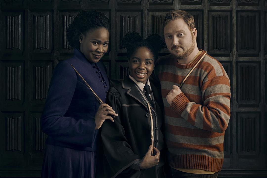 Retrato de Hermione, Rosa e Rony. Hermione usa um casaco roxo por cima de um vestido da mesma cor. Ela sorri e empunha sua varinha. Rosa está sorrindo também e com varinhas em mão, utilizando o uniforme de Hogwarts. Rony usa um suéter com listras roxas e brancas, e também segura a varinha.