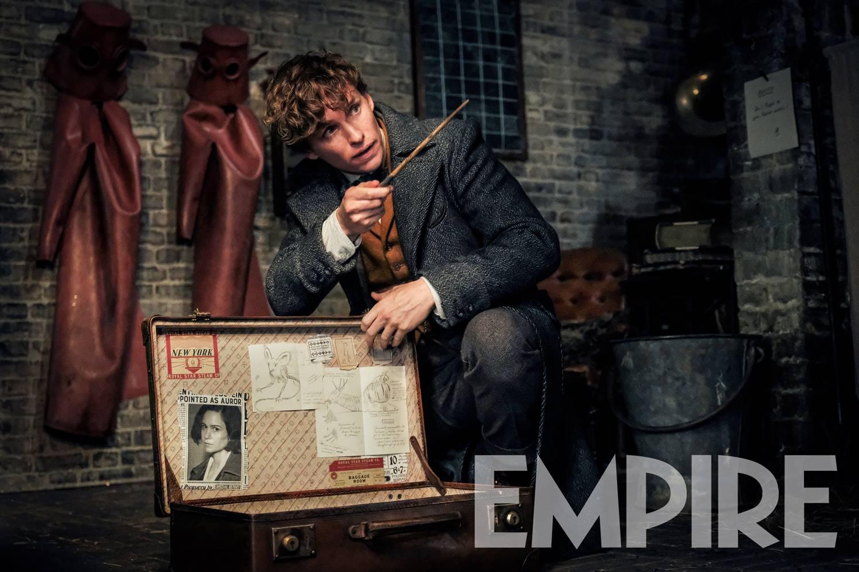 """Foto do ator Eddie Redmayne caracterizado como Newt Scamander no set de Os Crimes de Grindelwald. Ele usa um sobretudo cinza e, por baixo, um paletó mostarda. Ele aponta sua varinha para algo fora de quadro e, com a outra mão, segura a tampa da sua maleta. Na tampa, podemos ver desenhos e um recorte de jornal com uma parte de uma manchete que mostra """"POINTED AS AUROR"""", e embaixo, a foto de Tina Goldstein."""