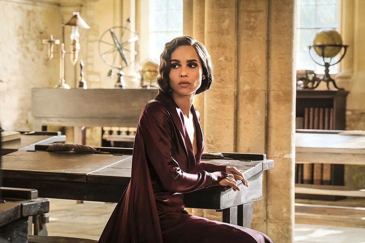 Foto do filme que mostra Leta em uma carteira de uma sala de Hogwarts. Ela usa um vestido cor de vinho.