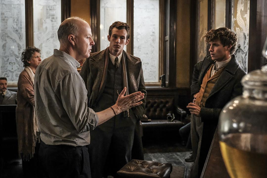 Foto mostra David Yates gesticulando para os atores Eddie Redmayne e Newt Scamander. Eles estão em uma sala com várias janelas claras. Os dois atores usam casacos e prestam atenção no diretor.