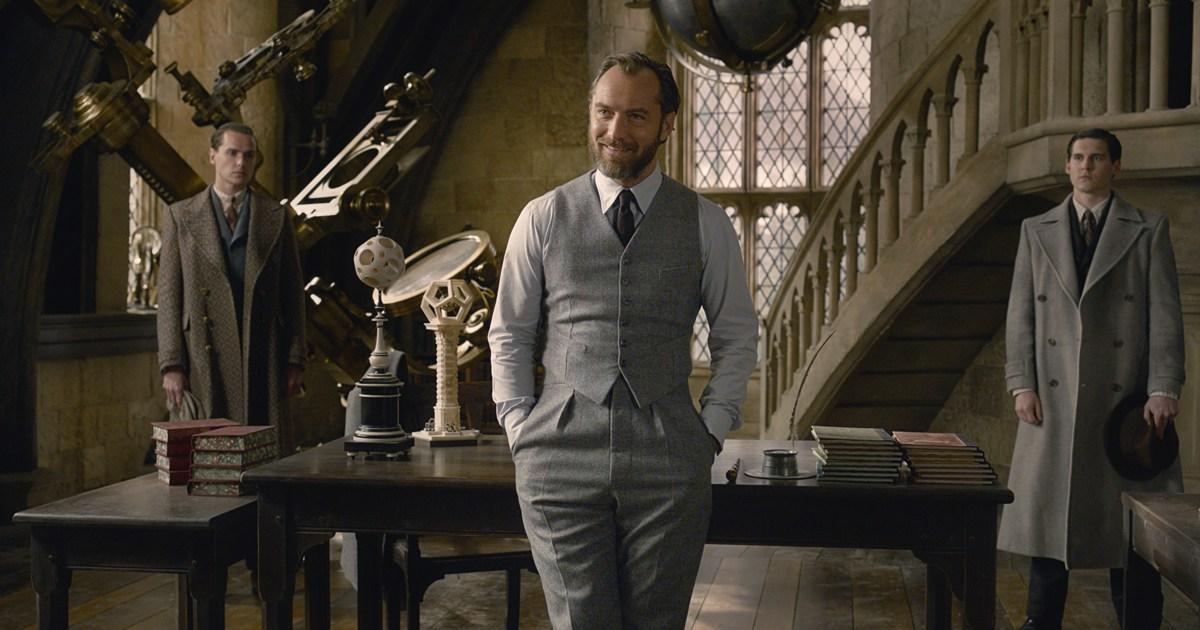 Alvo Dumbledore em 1927 na sala de aula de Defesa Contra as Artes das Trevas. Ele está apoiado numa mesa e, ao fundo, vemos duas pessoas do Ministério.