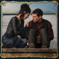 Credence está sentado, um pouco cabisbaixo, num teto de uma casa. Seu rosto está apontando para a direita, na direção da Maledictus, que parece confortá-lo. Ela está acocorada ao lado do personagem.
