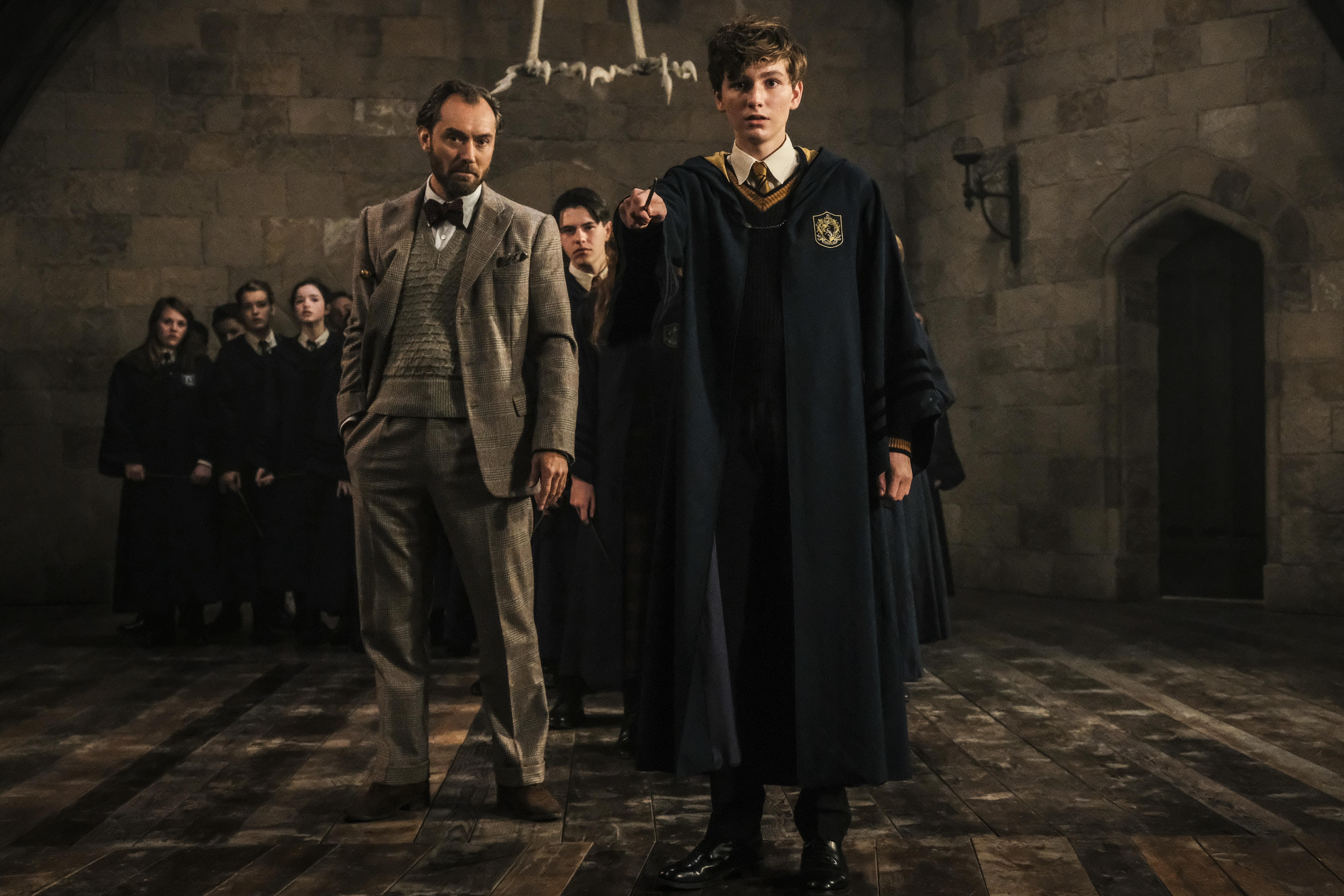 Foto promocional de Animais Fantásticos: Os Crimes de Grindelwald. Na imagem, Dumbledore ensina um jovem Newt. A sala está repleta de alunos ao fundo.