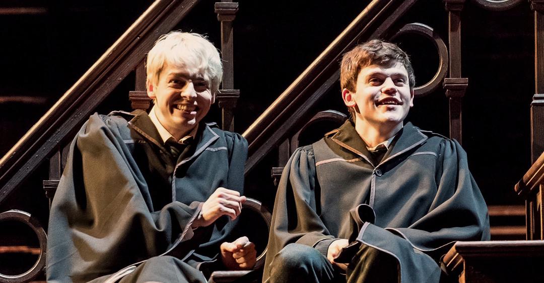 Foto da peça Criança Amaldiçoada. Os personagens Alvo e Escórpio estão sentados juntos, rindo, numa escada.