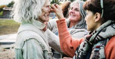 Foto: duas mulheres retocam a maquiagem do ator Brontis Jodorowsky, que interpreta Nicolau Flamel. Sua caracterização é com muitas rugas na cara, cabelos brancos e vestes totalmente brancas, mas aparentemente velhas.