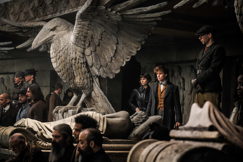 Newt (Eddie Redymane) e Tina (Katherine Waterston) lado a lado em um anfiteatro lotado. Na frente deles, um corvo de pedra enorme.