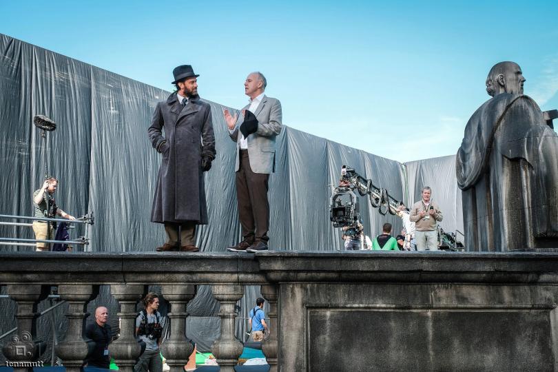 Jude Law conversa com David Yates, que segura um boné. Atrás deles há uma estátua, uma lona cinza, uma câmera e parte da equipe técnica.