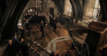 Uma cena está sendo filmada: um jovem Newt aponta sua varinha para o armário de um bicho-papão, em uma aula de Defensa Contra as Artes das Trevas de Dumbledore. Atrás dele, há uma fila. Parte da equipe técnica está visível, segurando microfones e manejando uma câmera.
