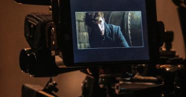 Eddie Redmayne como Newt Scamander aparece nas telas de uma câmera.