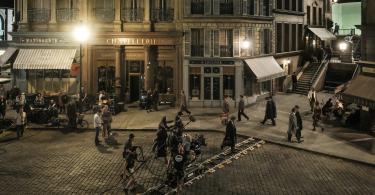 A equipe técnica filma transeuntes em uma calçada. Um fundo verde é visto ao fundo.