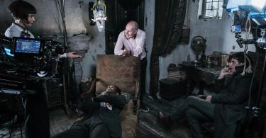 David Yates, curvado em um divã, sorri para Katherine Waterston, de pé. William Nadylam está deitado no divã, de braços cruzados, enquanto Eddie Redmayne está sentado ao lado, de pernas cruzadas.