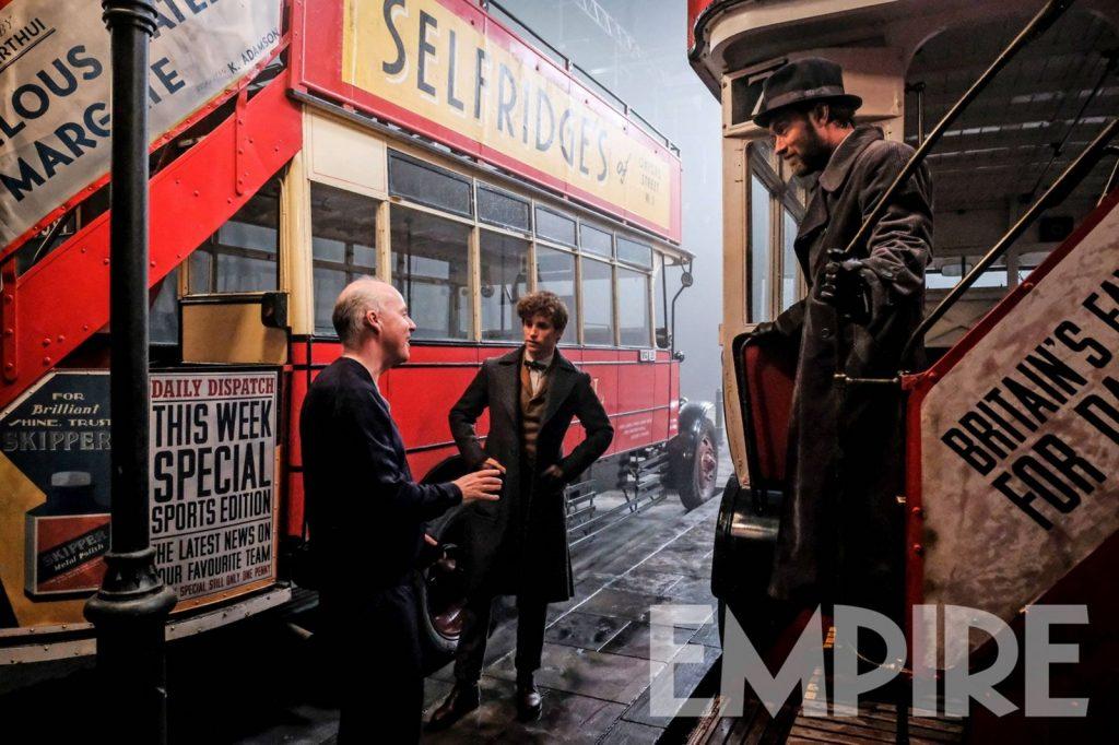 Foto dos bastidores de Os Crimes de Grindelwald. Vemos o diretor David Yates conversando com Eddie Redmayne e Jude Law. Eddie e Yates estão próximos a ônibus londrinos de dois andares e Jude Law está na escadaria de um deles, olhando para os dois.
