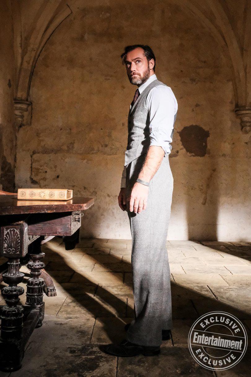 Dumbledore, de mangas arregaçadas, em uma sala de Hogwarts, ao lado de um grosso livro em uma mesa.