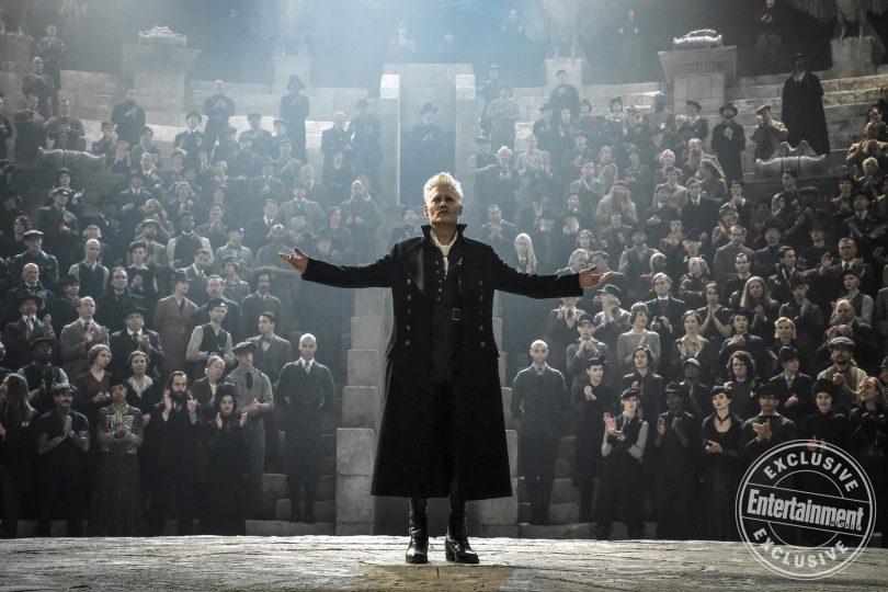 Grindelwald de braços abertos sendo aplaudido por um público em um anfiteatro.