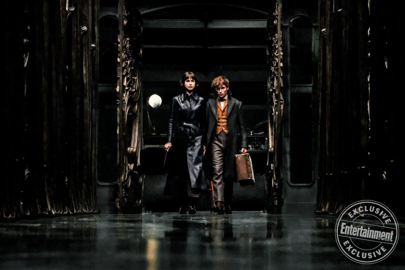 Tina e Newt, segurando sua maleta, andando em um dos corredores do setor de arquivos do Ministério das Relações Mágicas da França.