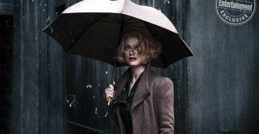 Queenie olhando para algo à sua frente parecendo preocupada. Está chovendo no local e ela segura um guarda-chuva.