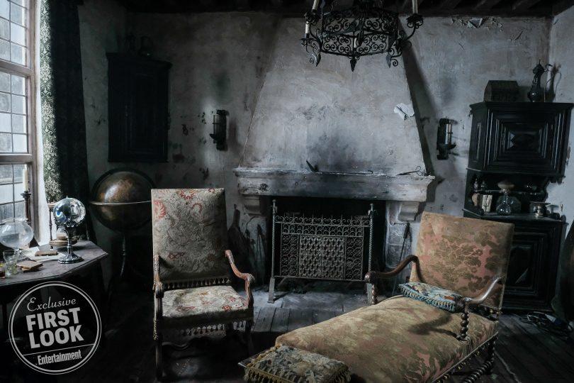 Casa de Nicolau Flamel. Um sofá e um divã estão do lado da lareira. Um globo está em uma mesa, perto de duas taças e uma ampulheta.