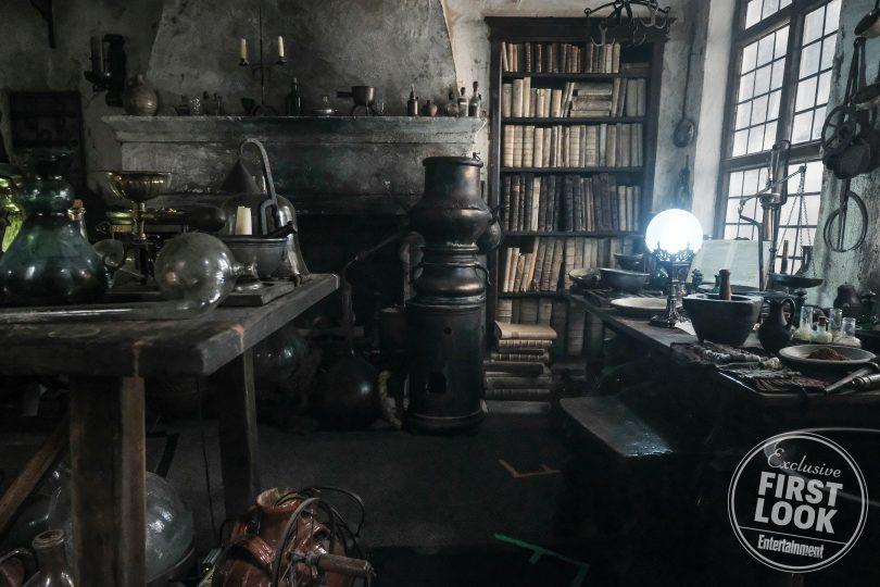 Casa de Nicolau Flamel. Diversos equipamentos de alquimia/química e livros estão em mesas e uma estante, Um globo brilha fortemente em uma das mesas.