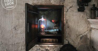 Casa de Nicolau Flamel. Em um cofre, estão um livro, papéis, um cálice e, dentro de uma redoma, a pedra filosofal, que brilha.