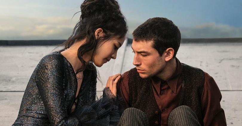 Nagini e Credence em foto promocional de Os Crimes de Grindelwald. Os dois estão no teto de algum prédio em Paris. Nagini, de joelhos, conforta Credence, que está sentado.