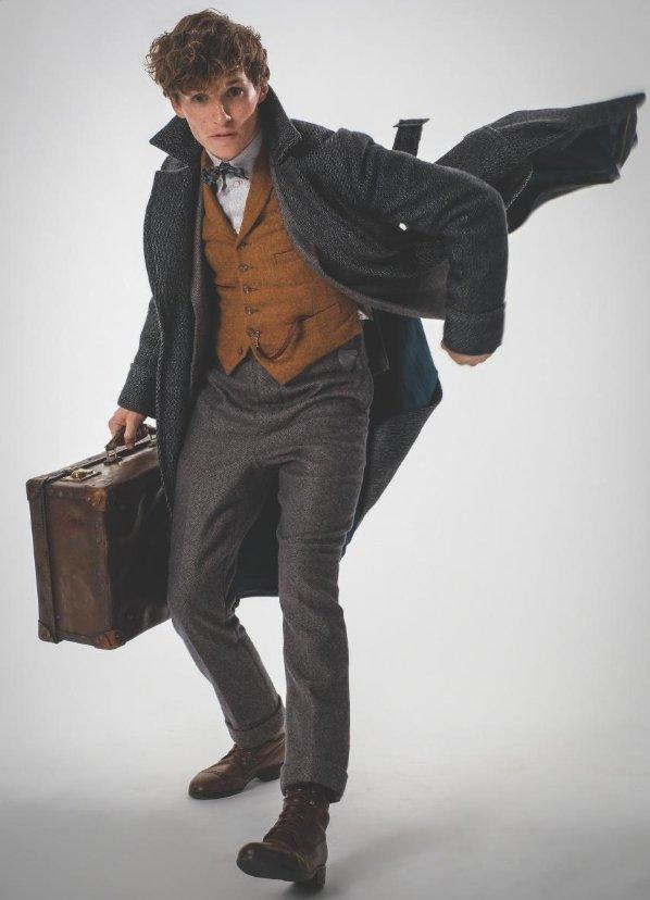 Ensaio fotográfico de Newt. Ele está em movimento e segura sua maleta.