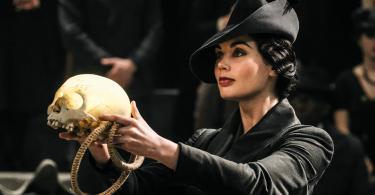 Na frente de um grande público, Vinda Rosier ergue um crânio e uma espécie de corda.