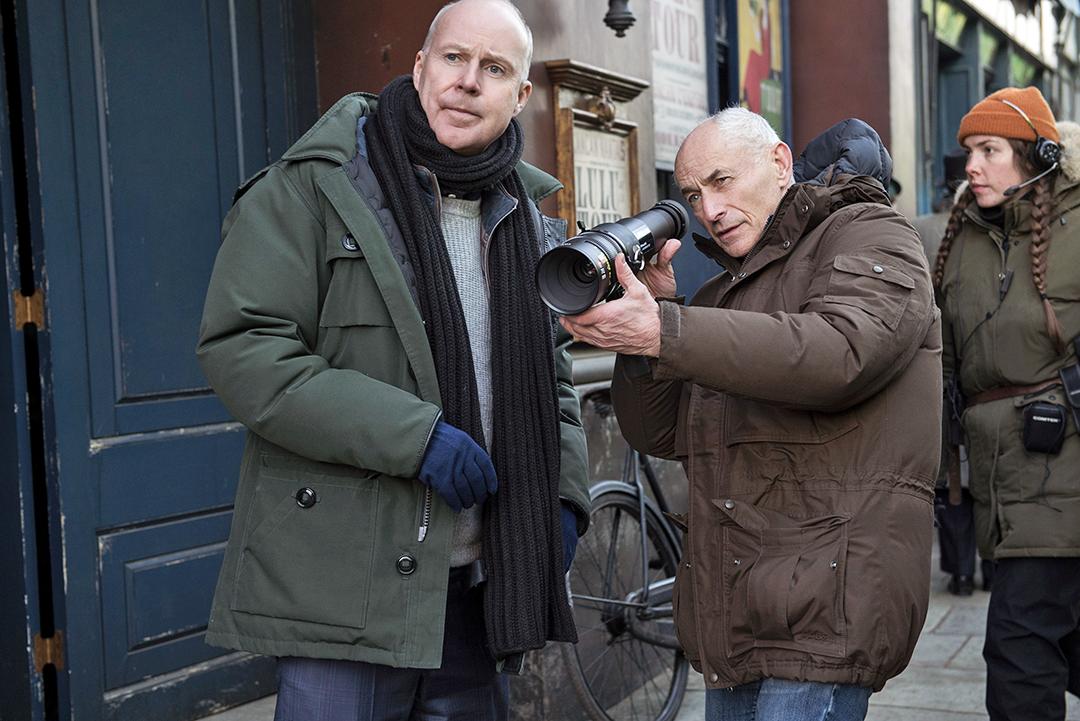 Foto de bastidores. David Yates observa um cenário e Philippe Rousselot conversa, com uma lente nas mãos.