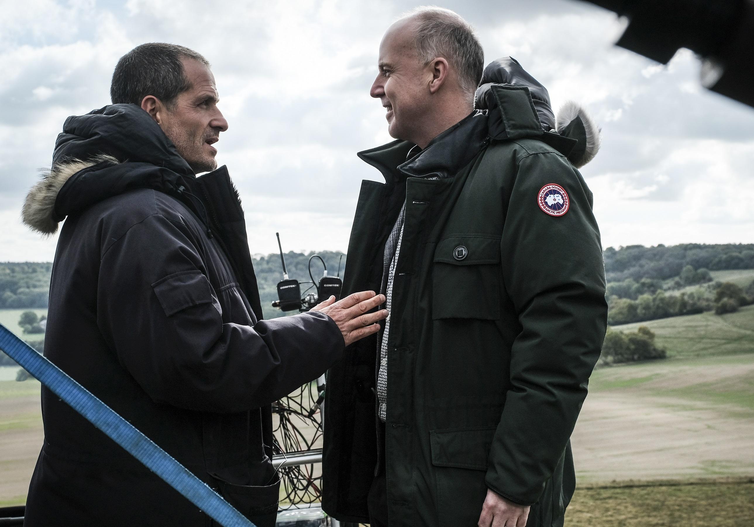 David Yates e David Heyman conversam em frente a uma paisagem de campo aberto.