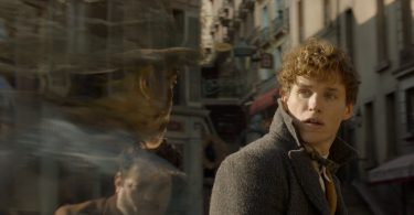 Newt e Jacob no meio da rua. Como num vulto, em imagem esmaecendo, Yusuf Kama parece falar com o protagonista.