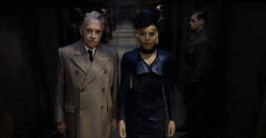Serafina Picquery e outro oficial olham para a frente. Eles estão num corredor cheio de guardas. Está escuro.