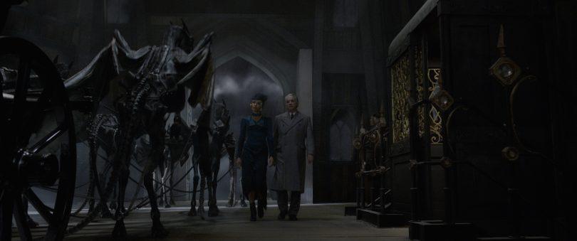 Serafina e um oficial ao lado de Testrálios. Há uma carruagem do outro lado deles.