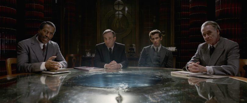 Teseu e outros três oficiais olham para frente, como se estivessem interrogando alguém. Na mesa, há algo que parece um líquido, mas não existe nenhum recipiente, ela parece fazer parte da mesa.