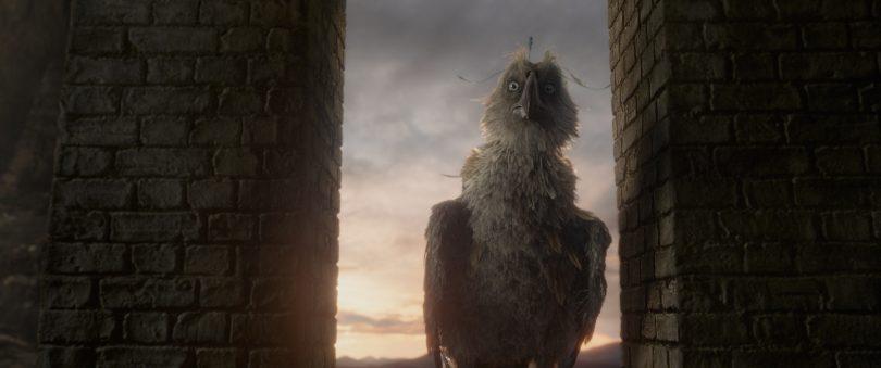 O agoureiro prostrado num vão entre pilastras. Há um céu de final de tarde ou de começo de manhã atrás dele.